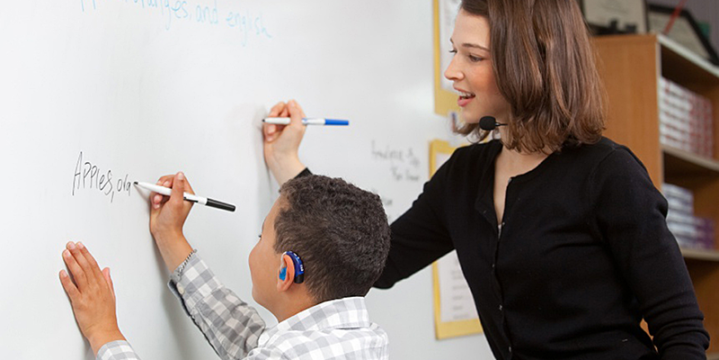 Teacher and child with a hearing aid at the whiteboard
