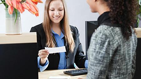 Seated bank teller helping customer