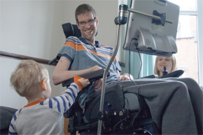 Man in wheelchair with young child looking on