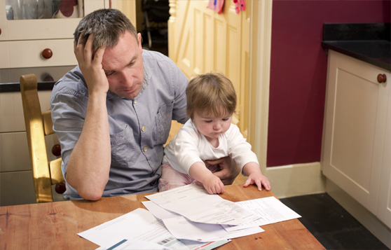 Man Paying Bills with young boy in his lap