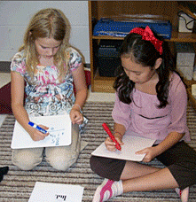 Two girls with low-tech dry erase boards